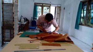 memotong bahan tas messenger